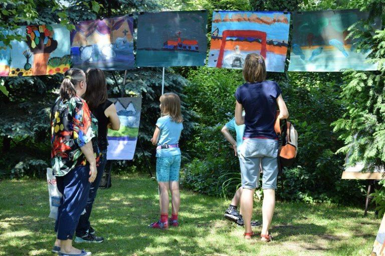 Kilka osób w tym dzieci stoją w ogrodzie tyłem oglądając wiszące obrazy.