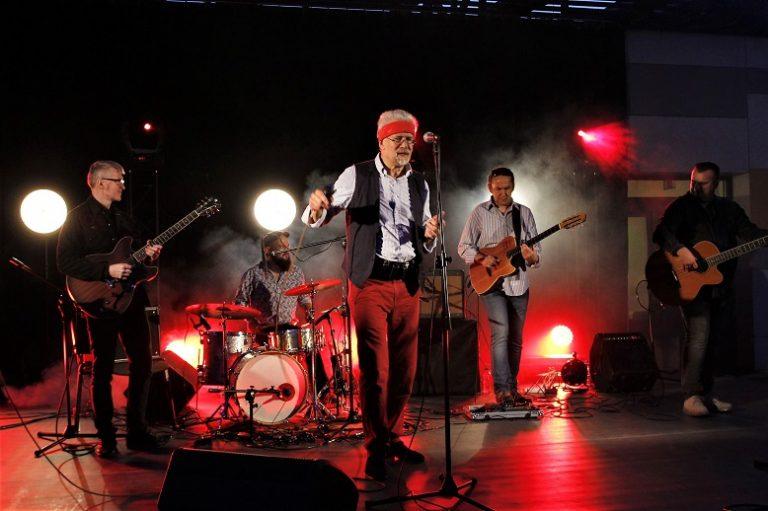 Kilku muzyków na scenie z instrumentami. Z przodu mężczyzna w czerwonej chustce na głowie. Stoi przed mikrofonem. Tło ciemne, oświetlone reflektorami.