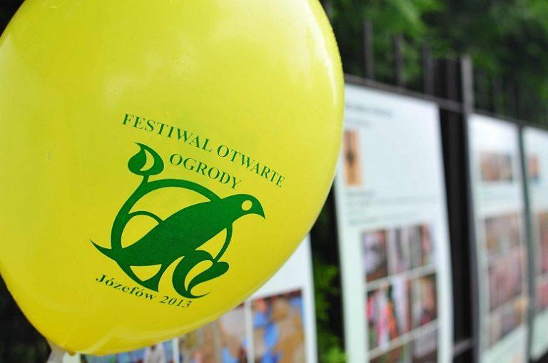 """Plener. Duży żółty balon z zielonym napisem """"Festiwal Otwarte ogrody"""". W tle plansze plansze wystawy zawieszonej na płocie."""