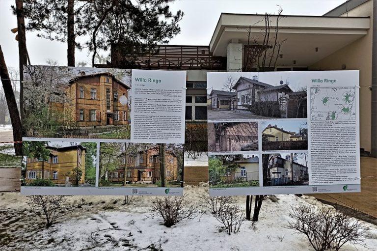 Plansze ze zdjęciami i opisami zawieszone jako wystawa plenerowa w parku przed budynkiem MOK Józefów