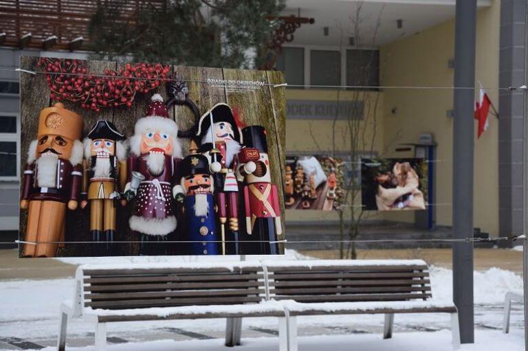 Fotografia zawieszona w plenerze przedstawiająca dziadki do orzechów. W tle park i budynek MOK Józefów.