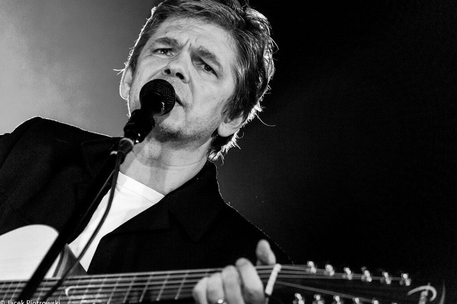 Mężczyzna w średnim wieku przy mikrofonie z gitarą. Czarno-biała fotografia.