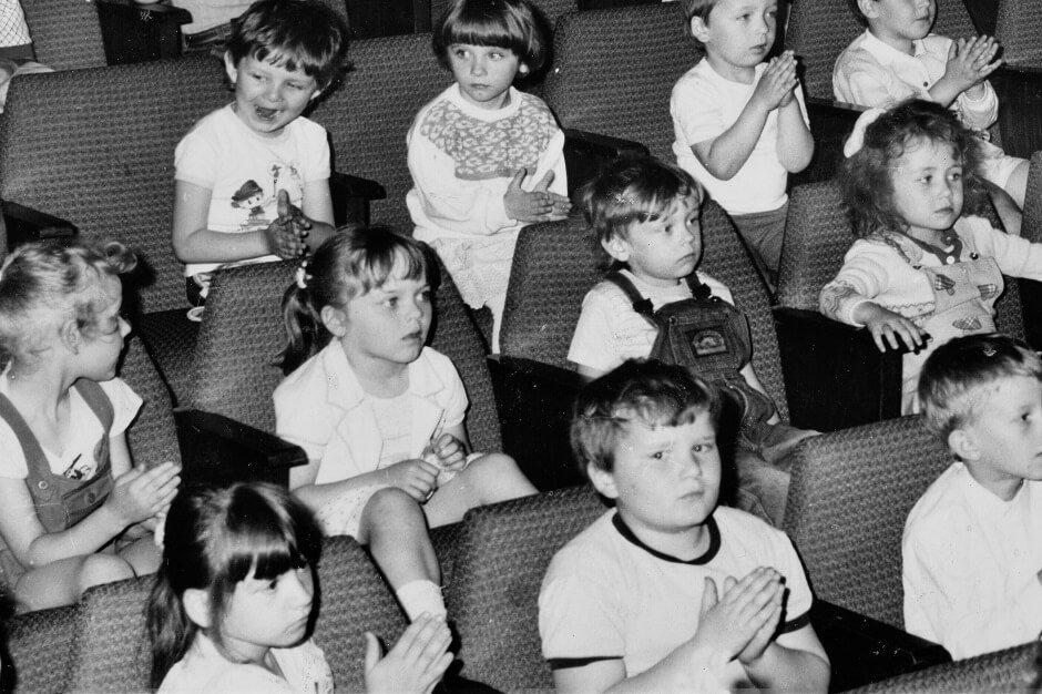 Czarno-białe zdjęcie. Widownia pełna siedzących kilkuletnich dzieci. Atmosfera zainteresowania.