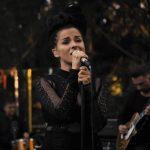 Młoda brunetka w czerni śpiewa do mikrofonu. Z tyłu muzycy z instrumentami. Plener. Las.