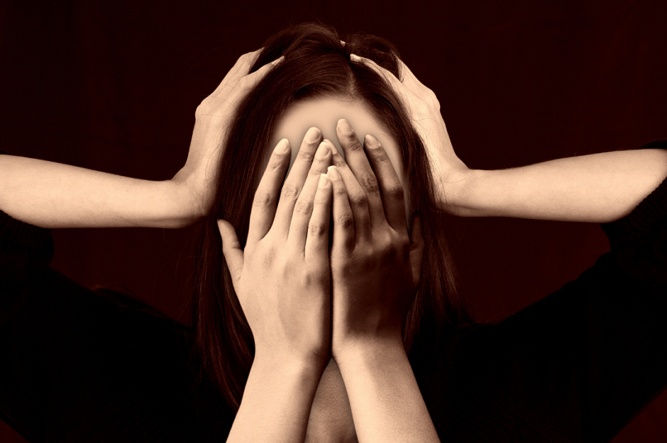 Kobieta zakrywa twarz rękoma. Dwie dodatkowe ręce trzymają jej głowę. Ciemne tło. Atmosfera stresu.