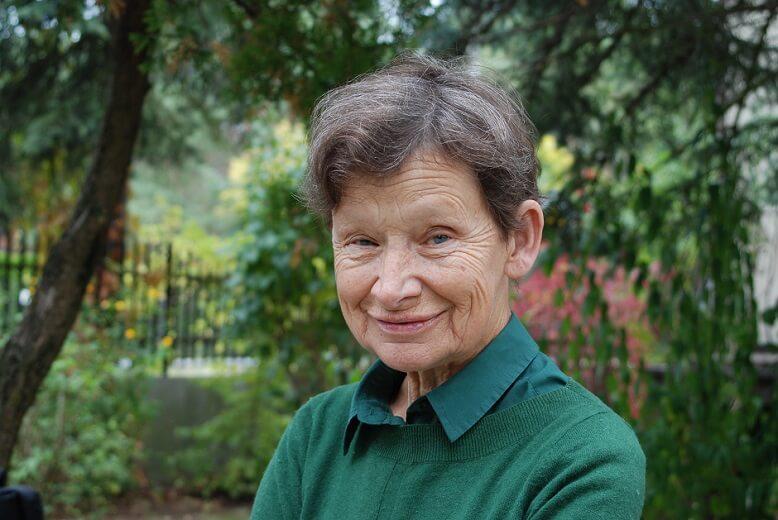 Uśmiechnięta starsza kobieta na tle zieleni. Plener.