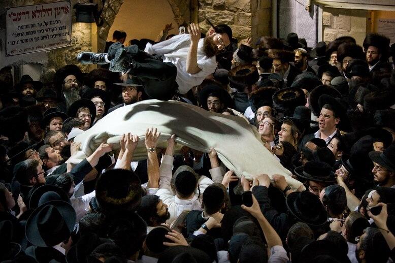 W tłumie chasydów kilku mężczyzn podrzuca na płachcie jednego z mężczyzn. Wnętrze.