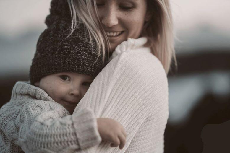 Uśmiechnięta kobieta trzyma na rękach uśmiechnięte dziecko.