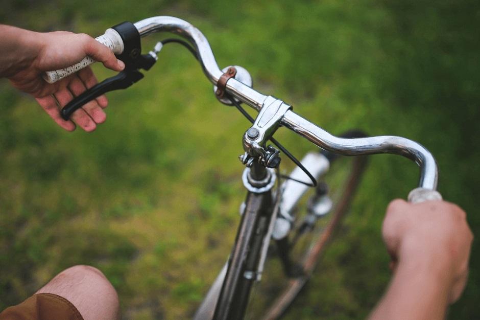 Ręce na kierownicy rowerowej. Plener.