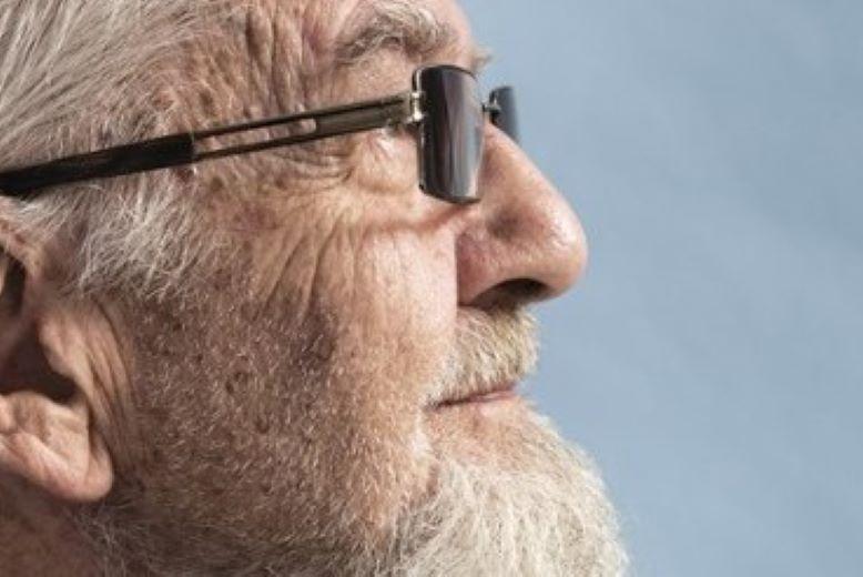 Profil starszego mężczyzny z brodą i w okularach.