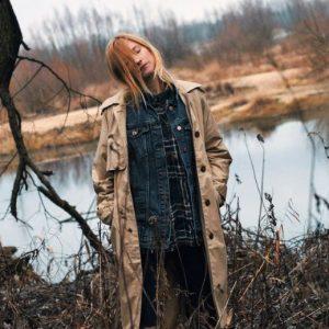 Blondynka w płaszczu stoi nad rzeką.