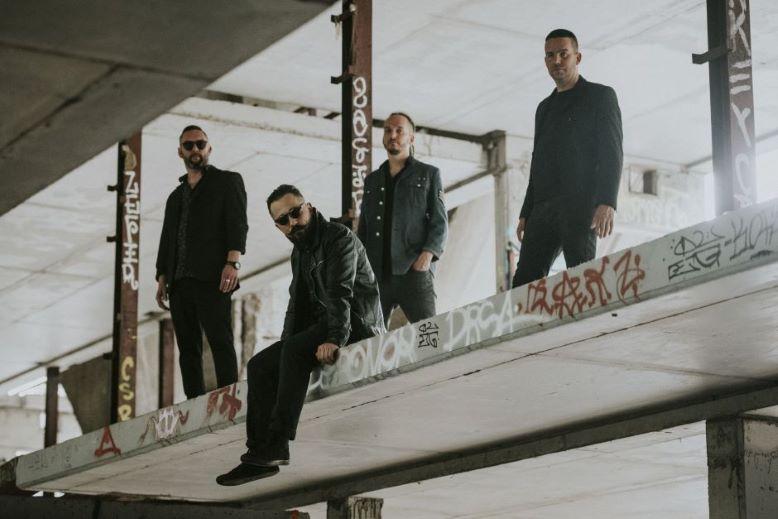 Czterech młodych mężczyzn stoi w miejskiej przestrzeni.