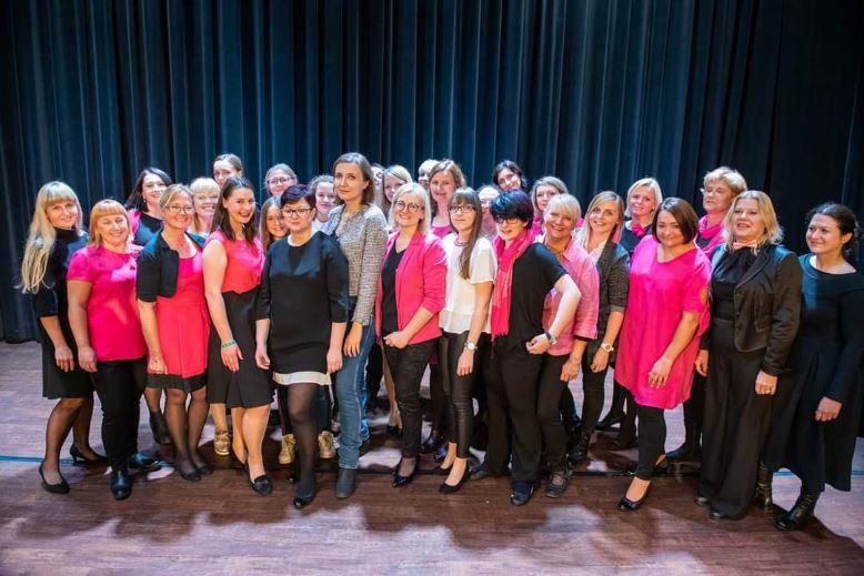 Grupa kilkudziesięciu kobiet pozujących na scenie do zdjęcia.