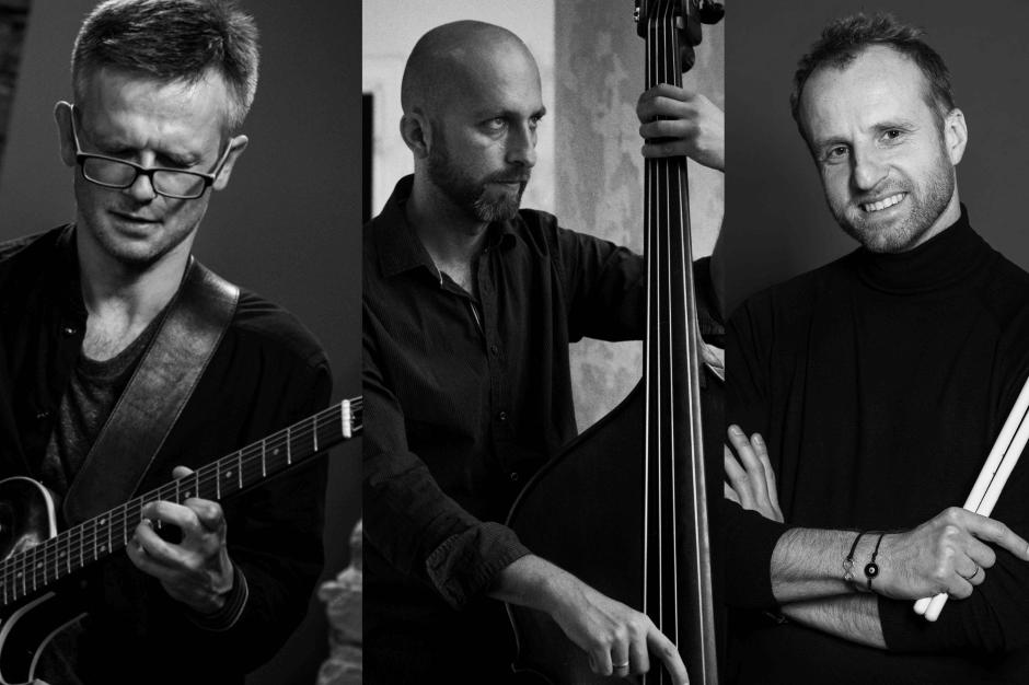 Czarno-białe zdjęcie. Trzech muzyków: gitarzysta, perkusista i kontrabasista.