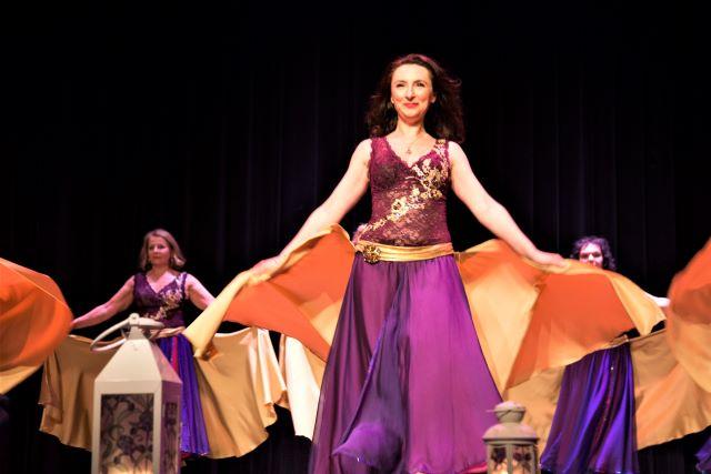 Grupa tancerek na scenie w fioletowo-pomarańczowych sukniach.
