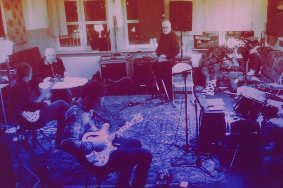 Kilku muzyków siedzi z instrumentami w sali z oknami.
