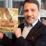 Uśmiechnięty mężczyzna trzymający w ręku książkę.