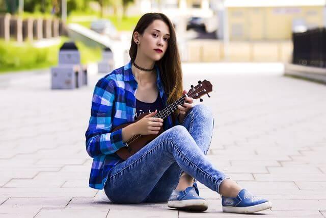 Nastolatka siedzi na chodniku i trzyma ukulele.