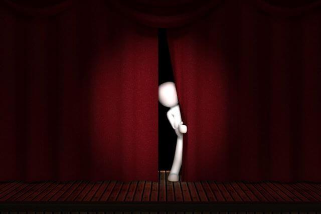 Animowana postać zagląda przez kotarę sceny w stronę widowni.