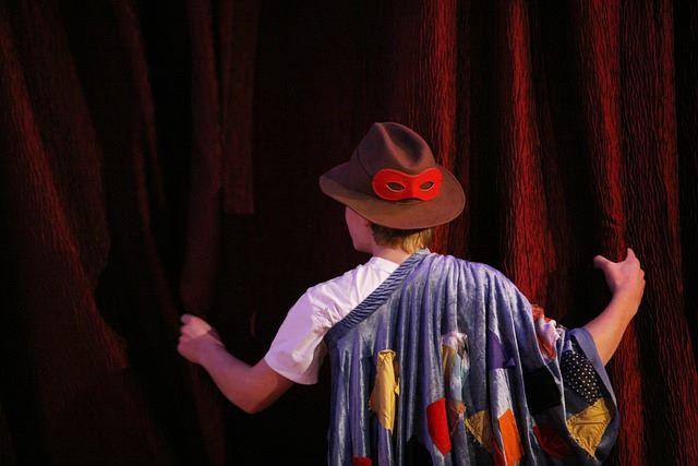 Chłopiec w kapeluszu i pelerynie trzyma zagląda za kurtynę teatralną.