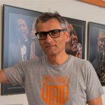 Mężczyzna w okularach na tle wiszących na ścianie zdjęć muzykó jazzowych.