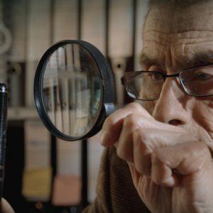 Starszy mężczyzna obserwuje pióro przez lupę.