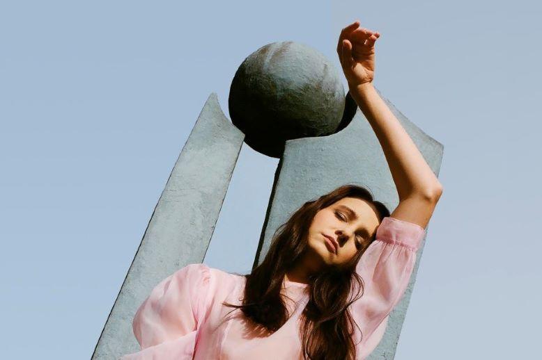 Kobieta pozuje na tle pomnika.