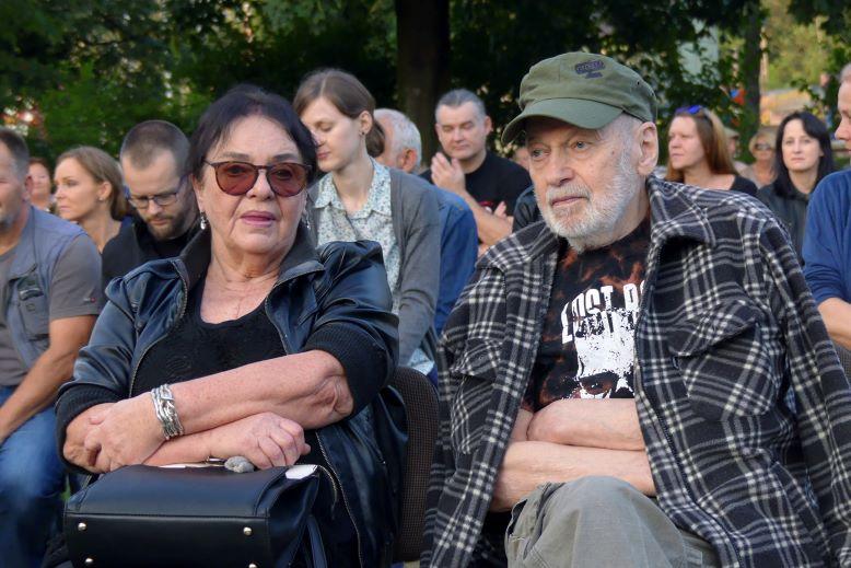 Mężczyzna i kobieta siedzą wśród publiczności. Plener.