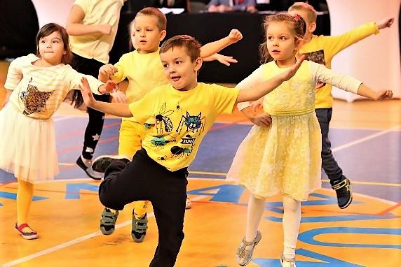 Dzieci tańczące w żółtych ubraniach.