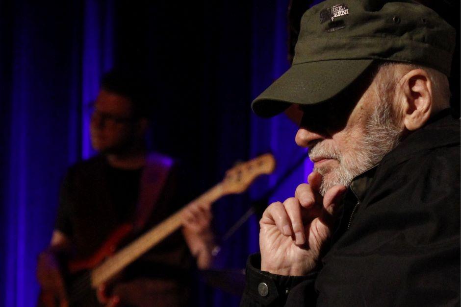 Mężczyzna w czapce z daszkiem na scenie.