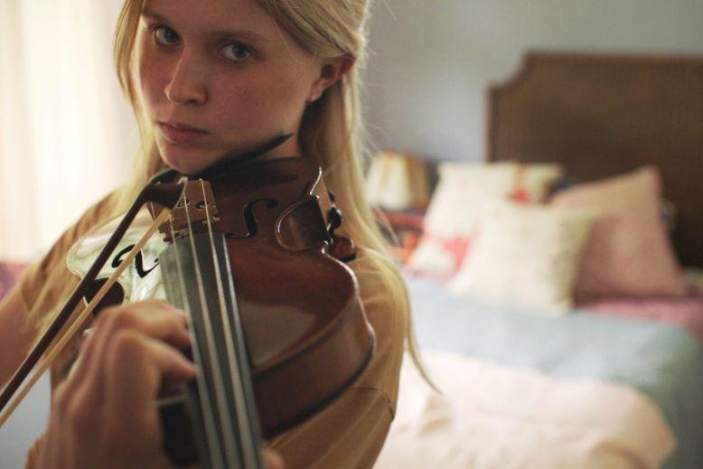 Dziewczyna trzyma w ręku skrzypce.