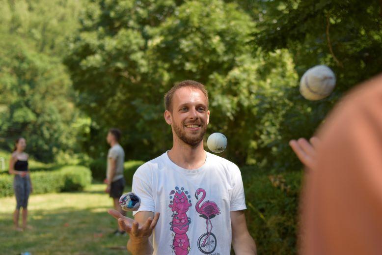 Uśmiechnięty mężczyzna żongluje piłkami.