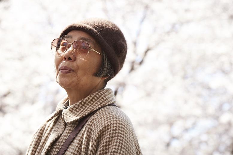 Starsza pani w kapeluszu na tle drzewa kwitnącej wiśni.