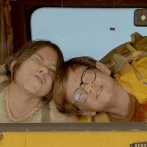Chłopiec i dziewczyna przylepieni nosami do szyby autobusu. Robią miny.