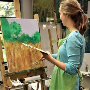 Dziewczyna malująca obraz na sztaludze.