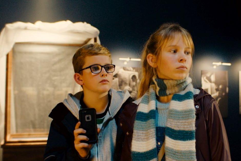Dwójka dzieci z latarką w sali muzealnej.