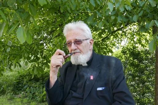 Starszy mężczyzna z brodą pali fajkę w otoczeniu zieleni.