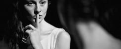 Czarno-białe zdjęcie młodej kobiety trzymającej palec na ustach. Ciemne tło.