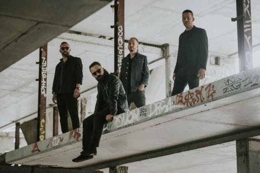 Czterech młodych mężczyzn w industrialnej przestrzeni.