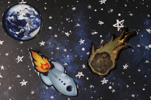 Kolaż ryzunkowy. Na gwieździstym niebie planeta, kometa i rakieta.