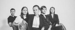 Czarno-białe zdjęcie pięciu osób siedzących w grupie i pozujących do zdjęcia.