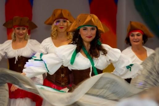 Uśmiechnięte cztery kobiety w żółtych kapeluszach i biąłych bluzkach na tle w biało-czerwone pasy. Poza taneczna.