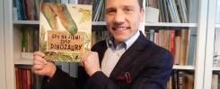 Uśmiechnięty mężczyzna trzyma książkę.