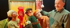Mężczyzna pokazuje kukiełkę babci-wilka mężczyźnie i kobiecie trzymającym kukiełki Czerwonego kapturka i myśliwego.