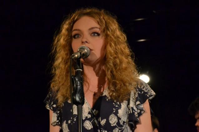 Dziewczyna o długich kręconych włosach stoi przed mikrofonem.