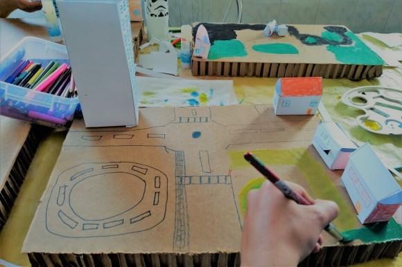 Stół, na którym stowi kartonowa makieta miasta. Dziecięca ręka rysuje ulice.