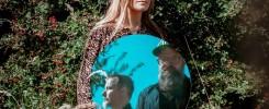 Plener. Kobieta trzyma lustro, w którym odbijają się sylwetki dwóch mężczyzn.
