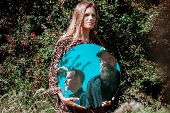 Kobieta na tle zieleni trzymająca lutro, w którym odbijają się dwaj mężczyźni.