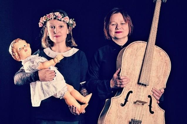 Dwie kobiety na czarnym tle. Kobieta z lewej z wiankiem na głowie trzyma na rękach lalkę. Kobieta po prawej trzyma w rękach kontrabas.
