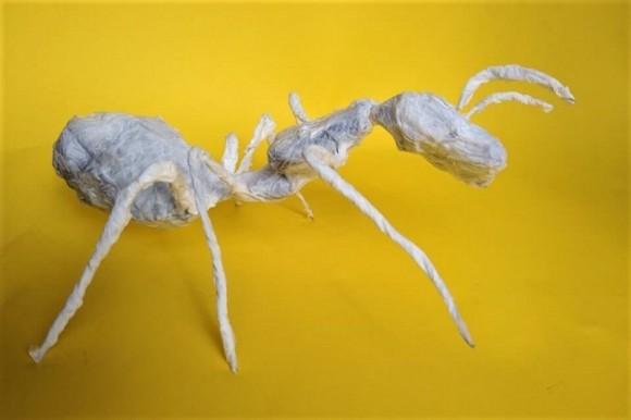 Biała papierowa rzeźba mrówki. Żółte tło.